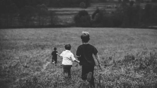 Three young boys running through a field of tall grass.