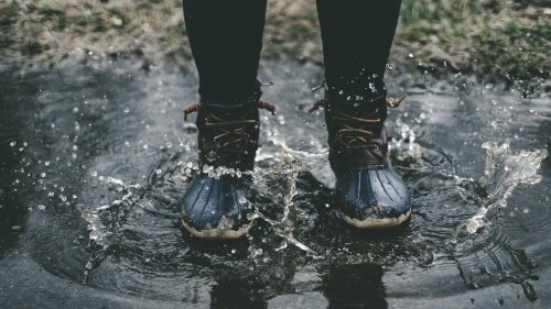A person wearing boots standing in a puddle.