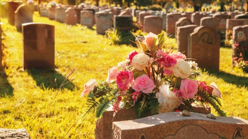 Headstones and flowers at a cemetery.