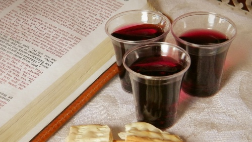 A Bible open to the book of John, small cups of wine and some broken unleavened bread.